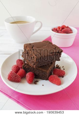 Vegan red kidney beans brownies Vegan red kidney beans brownies with raspberries on white plate on wooden table