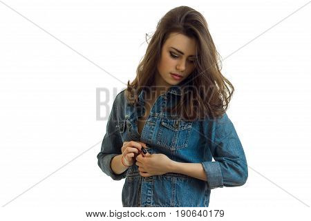 young beautiful brunette unbuttons jeans jacket with closed eyes isolated on white background
