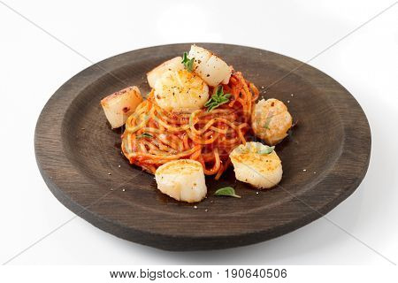 Pasta with fried scallops, oregano and tomato sauce on black wooden plate isolated on white background