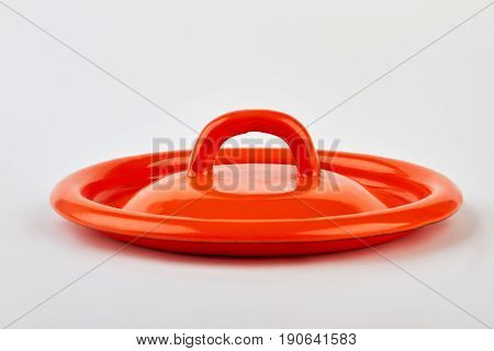 Front view of red lid. Single kitchenware object, white background.