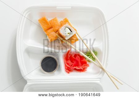Roll With Chopsticks, Rolls, Sushi. Chopsticks, Ginger, Soy Sauce In Container Delivery.