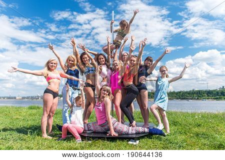 Portrait of women standing near pylon posing, having fun. Pole sport team