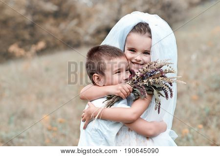 Young bride and groom playing wedding summer outdoor. Children like newlyweds. Little girl in bride white dress and bridal veil kissing her little boy groom, kids game. Bridal, wedding concept.