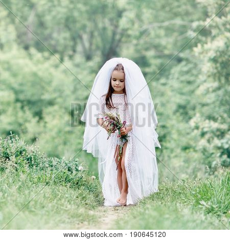 Young bride  playing wedding summer outdoor, newlyweds. Little girl in bride white dress and bridal veil posing over fresh greenery, kids game. Bridal, wedding concept, image toned and noise added.