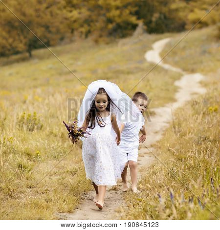 Young bride and groom playing wedding summer outdoor. Little girl in bride white dress and bridal veil walking with her little boy groom, kids game. Wedding concept, image toned and noise added.