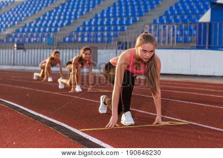 Young woman athlete at starting position ready to start a race