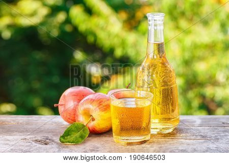 apple cider or juice in glass with ripe fresh apples on wooden table with green natural background. Horizontal shot with copy space. Refreshing summer drink