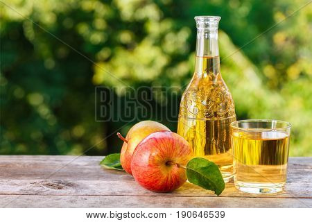 apple cider or juice in glass with ripe fresh apples on wooden table with green natural background. Horizontal shot. Summer drink