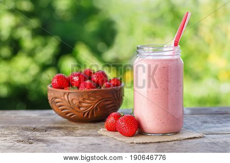 strawberry smoothie in jar and fresh ripe strawberries in bowl on wooden table with green natural bokeh on the background. Pink milkshake. Healthy summer drink concept. Berry cocktail. Still life