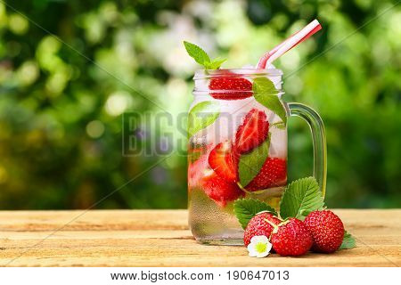 strawberry lemonade with ice and mint in mason jar on wooden table outdoor. Glass jar of summer refreshing  strawberry drink. Cold detox water with strawberry. Copy space