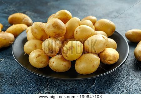 raw baby new potatoes in black plate.