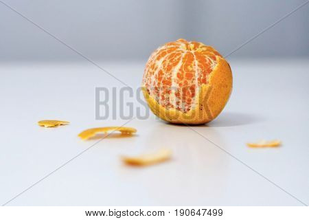 One fresh whole mandarin orange with leaf and one peeled and sectioned mandarin orange.
