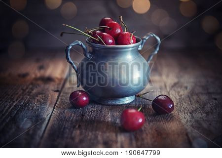 Cup of cherries on wood rustic background
