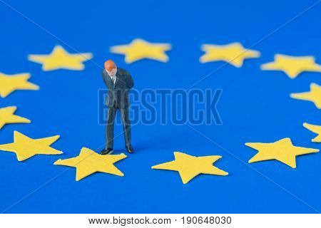 miniature people with businessman looking at one of twelve stars of euro flag use as europeon union or brexit concept.
