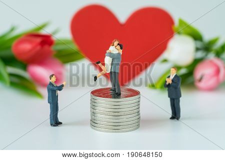 Miniature people with couple standing on top stack of coins and other clapping with the red heart symbol background as success love life concept.