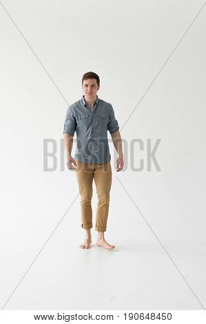 Young Handsome Man Of Strong Athletic Build, Dressed In A Shirt And Brown Trousers, Posing On White