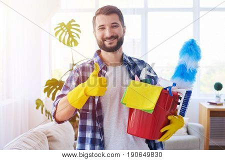 Close-up of cheerful bachelor holding cleaning set ant putting thumb up
