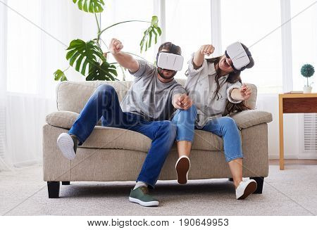 Wide shot of beautiful female and male driving in VR glasses while sitting on sofa