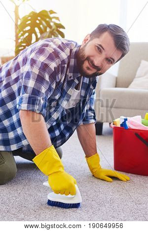Vertical of hardworking sir in gloves brushing carpet in spacy room
