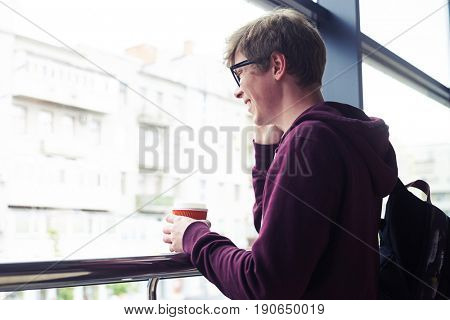 Mid shot of smiling man talking on phone and holding cup of coffee while leaning on handrail