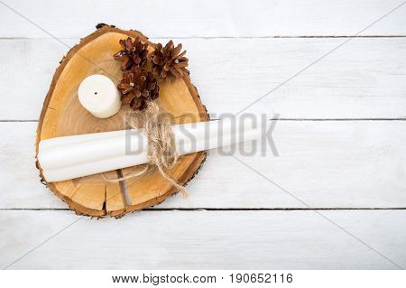 Cones and candles lie on a wooden stand on a white wooden background. View from above
