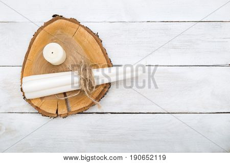 White candles lie on a piece of wood on a white wooden background