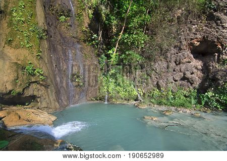 Turquoise blue pool under tranquil waterfalls surrounded by lush green tropical vegetation at La Conchuda waterfall in Rio la Venta Canyon Chiapas Mexico