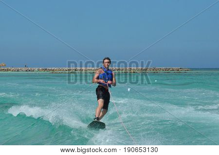 Guy wakeboarding and standing up in Aruba.