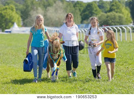 STOCKHOLM SWEDEN - JUNE 06 2017: Happy winning jockey of a pony gallop horse race and her proud family at Nationaldags Galoppen at Gardet. June 6 2017 in Stockholm Sweden