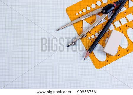 Mathematics class with compass, pencil, plastic template ruler on green paper graph in top view. Workplace of mathematics architect, constructor or designer. Engineering and Mathematics work tools for drawing.