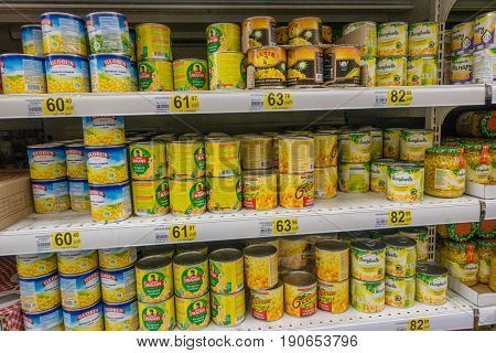 RUSSIA, MOSCOW, JUNE 11, 2017: Different types of canned corn on the shelves in the supermarket Auchan.