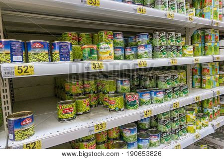 RUSSIA, MOSCOW, JUNE 11, 2017: Different kind of canned green peas on the shelves in the supermarket Auchan.