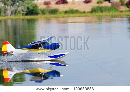 A floating Radio controlled model seaplane speeds up to take off on Guadiana river Badajoz