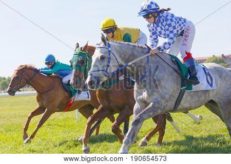 STOCKHOLM SWEDEN - JUNE 06 2017: Three jockeys side by side riding gallop arabian race horses at Nationaldags Galoppen at Gardet. June 6 2017 in Stockholm Sweden