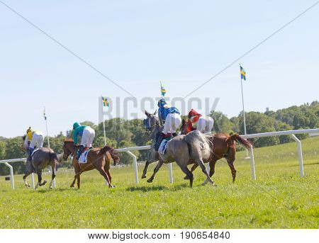 STOCKHOLM SWEDEN - JUNE 06 2017: Side rear view of standing colorful jockeys on gallop race horses riding swedish flags in the background at Nationaldags Galoppen at Gardet. June 6 2017 in Stockholm Sweden