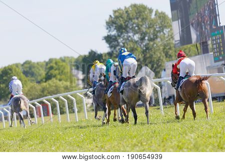 STOCKHOLM SWEDEN - JUNE 06 2017: Rear view of standing colorful jockeys on gallop race horses riding in a curve at Nationaldags Galoppen at Gardet. June 6 2017 in Stockholm Sweden