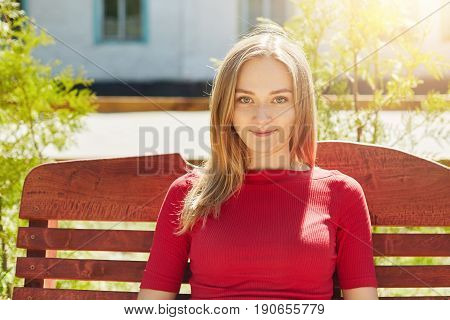 Horizontal portrait of fair-haired pretty young girl with freckles and blue eyes wearing red sweater sitting at bench in park admiring summer weather and fresh air looking pleasantly into camera