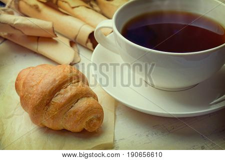 A fresh croissant a cup of coffee and old scrolls. Close-up. Concept: Learning / Memories / Break / Solitude / Relax /