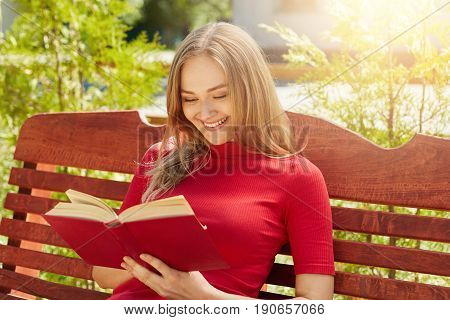 People rest hobby vacation concept. Cheerful fair-haired woman in red sweater holding her favourite book reading funny stories. Pretty female reading book at wooden bench admiring weather