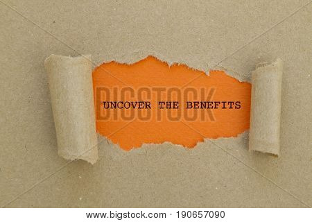 UNCOVER THE BENEFITS word written under torn paper .