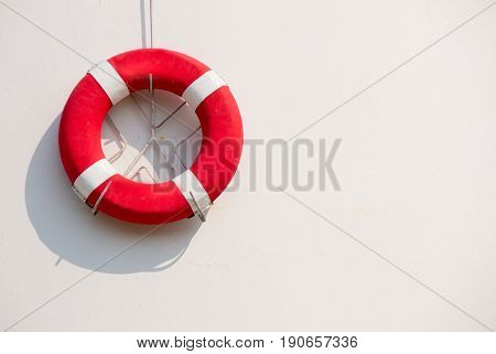 Red lifebuoy with white strip hanging on white wall , had space on left side for creative