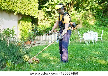 Professional gardener using an edge trimmer in the home garden