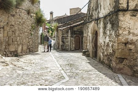 Senior couple walking in a medieval street in Trujillo Spain. Old town