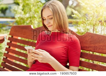 Freckled girl with straight hairstyle wearing red dress sitting in park at bench using her cell phone surfing social networks and downloading pictures. Sunny weather bright colors beautiful nature