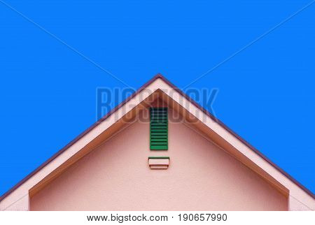 Pink house wall gable roof and blue sky