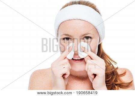 Smiling Woman With Freckles Wiping Her Face With Cotton Pads On White Background