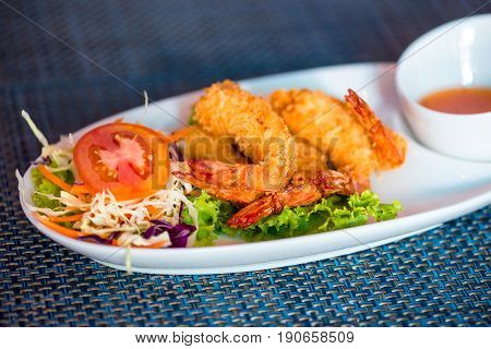 Shrimp In Batter With Sweet-sour Sauce On A Close-up Plate