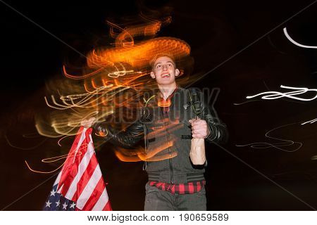 Guy celebrate Independence Day at night. Hapy smiling man with alcohol and with american flag on blurred city lights background. Youth lifestyle concept
