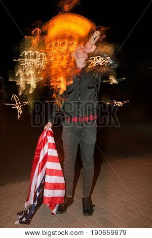 Guy celebrate Independence Day at night. Man with alcohol and with american flag on blurred city lights background. Youth lifestyle concept
