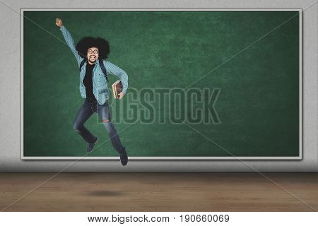 Young afro man jumping and lifting hand while holding book in the classroom